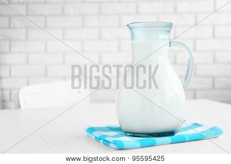 Pitcher of milk on wooden table, on bricks wall background