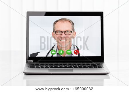 Close-up Of Videoconferencing With Male Doctor On Laptop At Desk