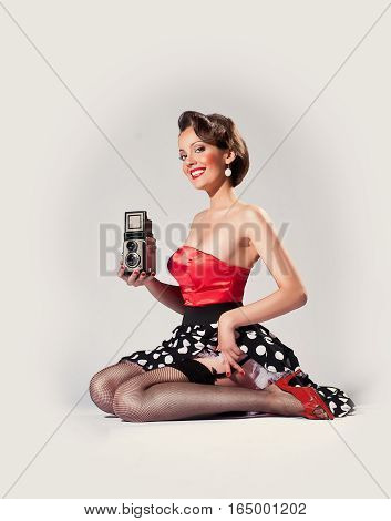 Pin up girl holds old TLR film camera from 1950