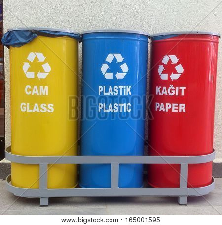Three recycle containers in different colours outdoor