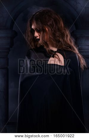 Beautiful Gothic Girl In A Black Cloak Against A Nightscape In The Cemetery