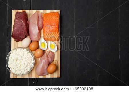 Proteins, fish, cheese, eggs, meat and chicken on a black background