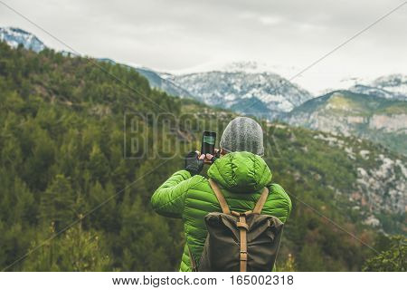Young man traveller wearing bright clothes making photo of green slopes and mountains with snowy peaks in Dim Cay district of Alanya on gloomy day, Antalya province, Mediterranean Turkey