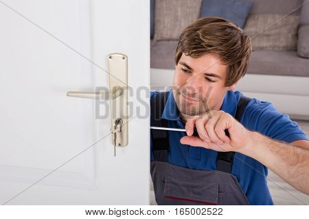 Handyman Fitting A New Door Using A Screwdriver At Home