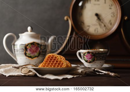 Breakfast with wafers and tea cup on table