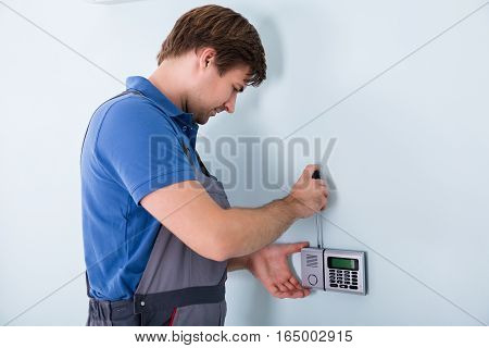 Young Male Repairman Fixing Security System Using Screwdriver At Home