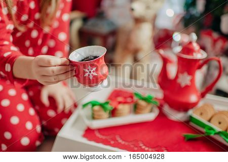morning tea from a red cup of tea and a child in red pajamas