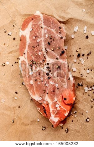 slice of raw pork shoulder with coarse salt and crushed peppercorn on brown kitchen paper