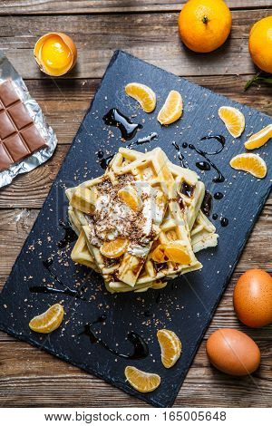 Breakfast with viennese waffles with topping, mandarin oranges, eggs on wooden table