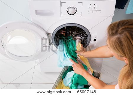 High Angle View Of Woman Loading Clothes From Basket In Washing Machine At Utility Room