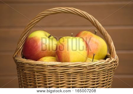 Many ripe red and yellow apples in brown wicker basket closeup