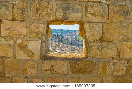 The window in old stone wall shows the old Jewish cemetery on the Mount of Olives Jerusalem Israel.