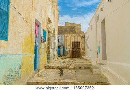 The small yard in old residential neighborhood of El Kef with crumbling walls and wooden doors Tunisia.