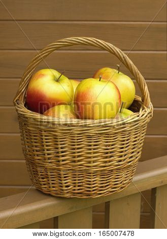 Many red and yellow apples in small brown wicker basket vertical view