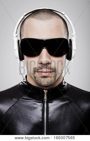 Portrait of futuristic man listening to music with headphones over white background