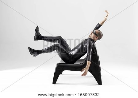 Futuristic man seated on a black chair over white background