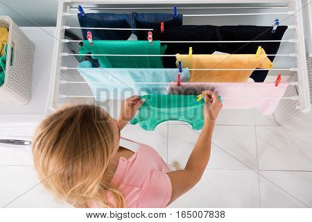 High Angle View Of Woman Hanging Wet Clean Cloth On Clothes Line At Laundry Room