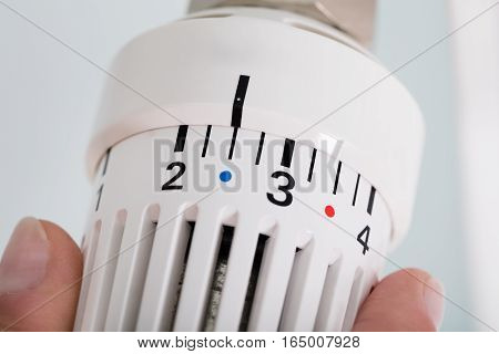 Close-up Of Person Hands Adjusting Thermostat Radiator Valve