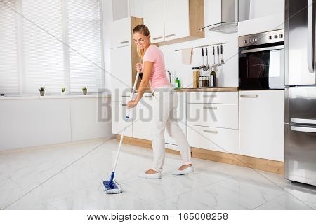 Smiling Cleaning Service Woman With Mop Cleaning Floor In The Kitchen At Home