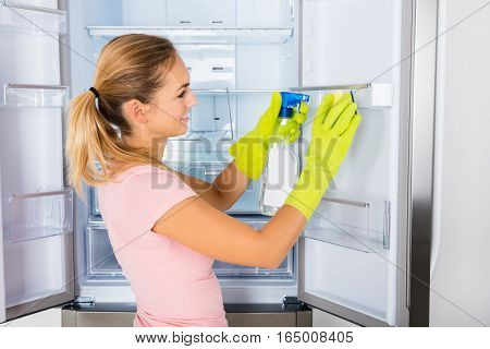 Young Happy Housewife Woman Cleaning The Empty Refrigerator Door With Spray Bottle And Sponge