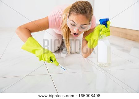 Shocked Young Woman Removing Stain On The Floor With Brush And Spray Bottle At Home