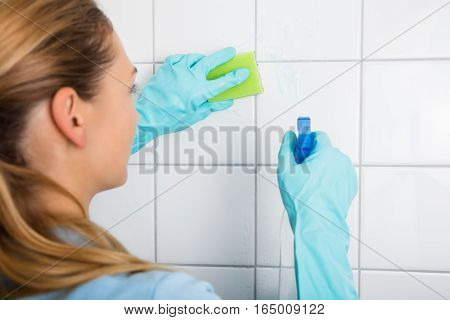 Cleaning Service Professional Woman Cleaning The Tiled Wall Using Sponge And Spray Bottle