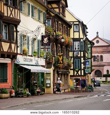 COLMAR, ALSACE / FRANCE - OCTOBER 26, 2016: Famous  half-timbered houses decorated with flowers, store signs and advertisements in the city center