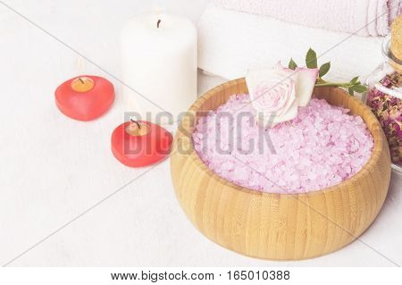 Bath salt with aroma of a rose in a wooden bowl petals and a fresh pink rose towels and candles on a white background. Toning.