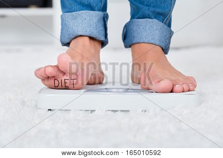 Close-up Of Person Feet Standing On Weighing Scale Showing Diet Text At Home