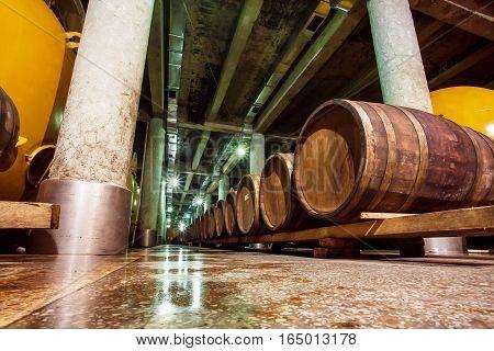 KVARELI, GEORGIA - OCT 3, 2016: Wine cellar with old oak barrels and metal cisterns of the Kindzmarauli Corporation Wine House on October 3, 2016. Winery produces 25 varieties of wine and 10 brandies