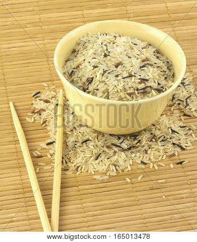 China color rice and beige bowl on brown straw mat with chopsticks closeup