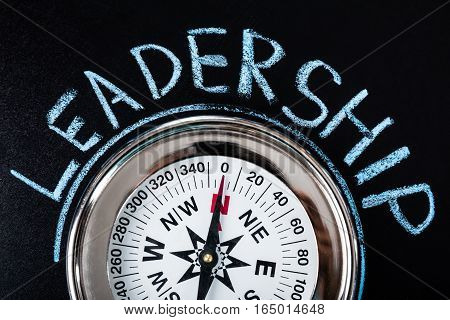 Close-up Of Compass With Leadership Text On Blackboard