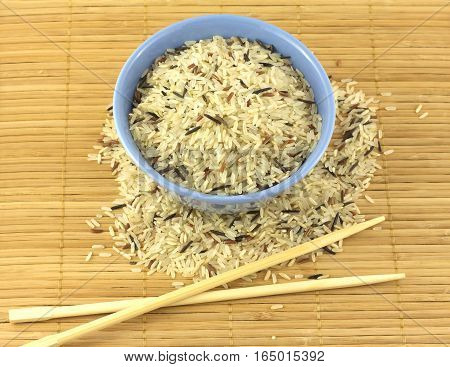 China color rice and blue bowl on brown straw mat with chopsticks closeup
