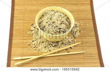 China color rice in beige bowl on brown straw mat with chopsticks isolated on white closeup