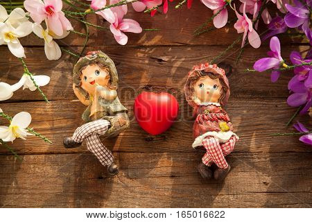 Statues of boy and girl with colorful heart between them on wooden background with flowers. Valentines day concept with couple in love.