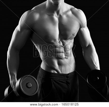 Working those muscles. Cropped black and white shot of a ripped muscled man lifting weights shirtless