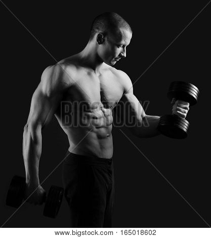 Perfecting his shape. Studio monochrome portrait of a shirtless hot and sexy masculine male bodybuilder pumping iron