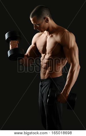 Focused on fitness. Masculine shirtless male pumping iron showing off his sexy ripped body