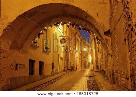 VILNIUS, LITHUANIA - JANUARY 2, 2017: Kazimiero street by night with an arcade in the foreground