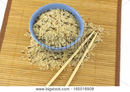 China color rice in blue bowl on brown straw mat with chopsticks closeup