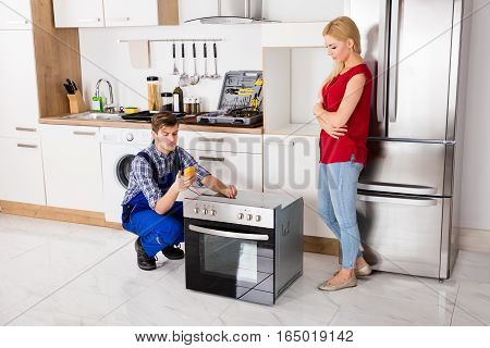 Male Worker Repairing Oven Using Multimeter With Young Woman Standing In Kitchen