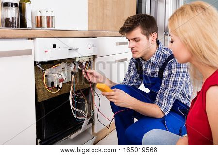 Young Woman Looking At Male Technician Checking Dishwasher With Digital Multimeter In Kitchen