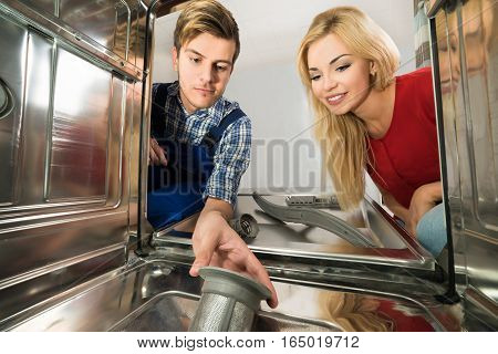 Young Woman Looking At Male Worker Repairing Dishwasher In Kitchen