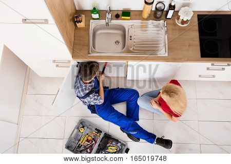 High Angle View Of Young Woman Looking At Male Worker Repairing Kitchen Sink At Home
