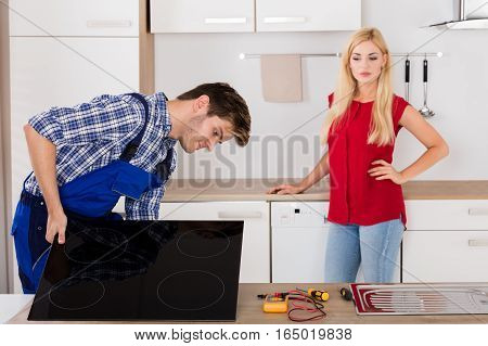 Male Repairman Installing Induction Cooker With Young Woman Standing In Kitchen