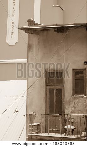 Poverty and wealth together and always close - balcony with old chair sepia
