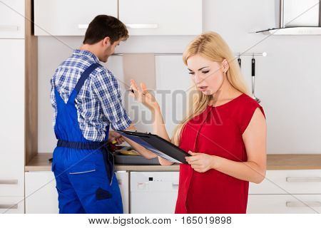 Young Frustrated Woman Looking At Expensive Bill On Clipboard With Plumber Standing In Kitchen