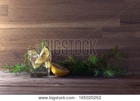 Gin With Lemon, Ice And  Juniper Branch On A Old Wooden Table