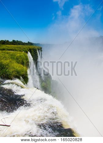 Close view from one of the water falls in Cataratas del Iguazu park, with a blue sky and a lot of water in the air, misty.