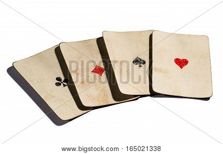 Four aces old withered cards of all suits spread out isolated on white background